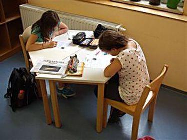 Bild mit zwei Kindern am Tisch bei den Hausaufgaben